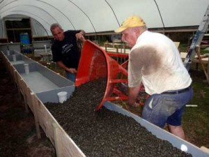 Practical Aquaponics loading the gravel into the grow beds.